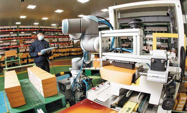 KT가 충북 제천 자동차 부품 제조기업에 구축한 스마트공장 협동로봇이 베어링 박스에 테이프를 붙이는 작업을 하고 있다. /고운호 기자