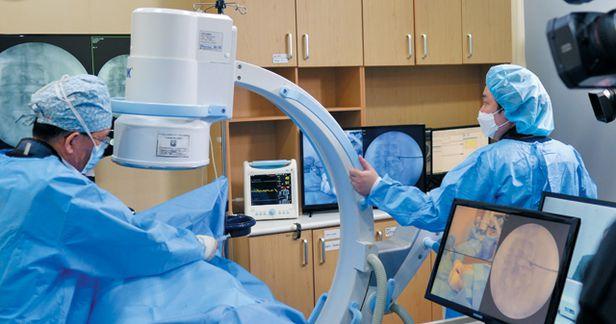 문동언통증의학과의원 의료진이 관상동맥질환으로 척추수술이 힘든 70대 척추관협착증 환자에게 추간공성형술 시술을 하고 있다. 특수 개발된 키트로 진행된 시술은 온라인으로 생중계됐다. /문동언통증의학과의원 제공